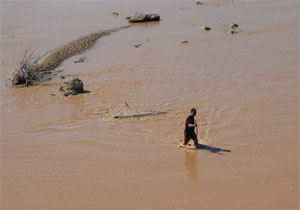Man walking crossing the river Oued Ksob